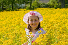 Girl Smiling in Front of Flowers. Girl in Dress Smiling in a Field of Flowers Stock Photo