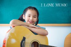Girl smiling with guitar in school classroom. Pretty asian girl smiling with guitar in school classroom stock images
