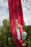 Girl smiling while hanging from fabric Royalty Free Stock Photo
