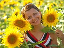 Girl smiling happy. In a field with sunflowers Royalty Free Stock Photo