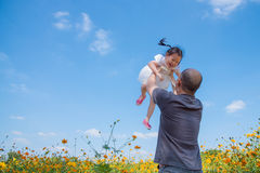 Girl smiling between her father throw her to the air Stock Image