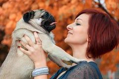 Girl smiling at her pug pet dog Royalty Free Stock Image