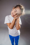 Girl smiling in his sleep hands on face over gray Royalty Free Stock Photography