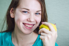 A girl is smiling and holding an apple in her hand Stock Images