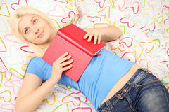 Girl smiling and holding a book in bed Royalty Free Stock Image