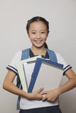 Girl smiling and holding bunch of notebooks and digital tablet, Studio Royalty Free Stock Photos