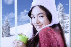 Girl smiling while holding hot drink Stock Photos