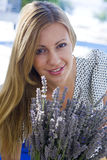 Girl smiling and holding a lavender. Preaty girl smiling and holding a lavender Royalty Free Stock Images
