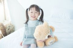 Girl smiling while hugging stuffed bear on bed Stock Images
