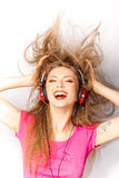 Girl smiling while listening music on headphones Stock Photography