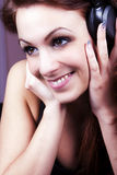 Girl smiling and listening to music on headphones. Royalty Free Stock Photos
