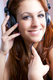 Girl smiling and listening to music on headphones. Royalty Free Stock Photo