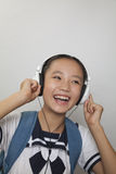 Girl smiling and listening to music, Studio Stock Photography