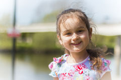 Girl smiling. Little girl with a bridge blurred in the background with a lovely smile on her face Stock Photos