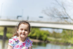 Girl smiling. Little girl with a bridge blurred in the background with a lovely smile on her face Royalty Free Stock Images