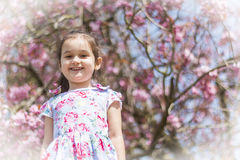 Girl smiling. Little girl standing in front of a gorgeous tree with a lovely smile on her face Royalty Free Stock Images