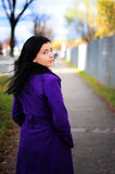 Girl smiling looking back. Beautiful woman  walking down street, looking back. Shallow Depth of field Royalty Free Stock Photos