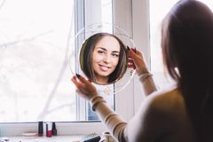 Girl smiling looking in the mirror. Young beautiful girl smiling looking in the mirror stock image