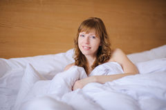 Girl smiling while lying in bed. Red-haired girl in bed covered with  blanket and smiling Royalty Free Stock Photo
