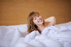 Girl smiling while lying in bed Royalty Free Stock Photos