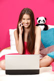 Girl smiling and making a call in her pink room Royalty Free Stock Photo