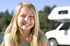 Girl (9-11) smiling, motor home in background, portrait Stock Photo