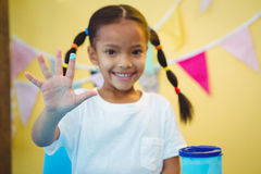 Girl smiling with paint on her finger Royalty Free Stock Photo