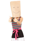 Girl in smiling paper bag on head with thumbs up Royalty Free Stock Photo