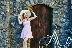 Girl smiling in pink dress, straw hat posing portrait, standing near textured stone, old wall and wooden door royalty free stock photos