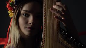 A girl on a dark background plays a traditional bandura instrument. Girl smiling playing on pandora stock video