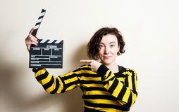 Girl smiling pointing out movie clapper on white background Royalty Free Stock Image