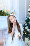 Girl smiling and posing at camera, holding candle on background Royalty Free Stock Photos