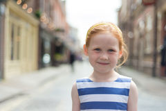 Girl (5) smiling in quiet street Royalty Free Stock Image