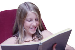 Girl smiling when reading book stock images
