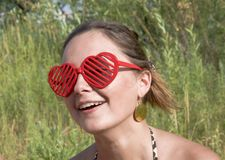 Girl smiling in red sunglasses Stock Images