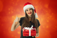 Girl smiling in santa hat with red gift Royalty Free Stock Image