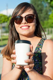 Girl smiling and showing cup of takeaway coffee Stock Photography