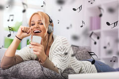 Girl smiling and singing with her phone and headphones Stock Image