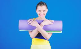 Girl smiling slim fit athlete hold fitness mat. Fitness and stretching. Stretching muscles. Getting into the yoga groove. Yoga as hobby and sport. Yoga class stock photo