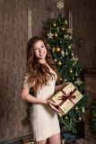 Girl genuinely joyfully smiling with a Christmas present in her hands is standing in a gold classic vintage dress Royalty Free Stock Photography