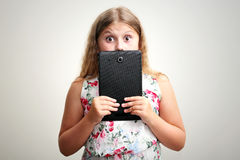 Girl smiling and surprised with tablet computer stock photography