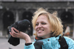 Girl smiling to pigeon Royalty Free Stock Image