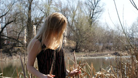 Girl smilling near river with glass Royalty Free Stock Image