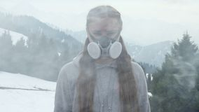 Girl in the smoke in a gas mask in the mountains. Girl in a gas mask in the smoke in the mountains stock video footage