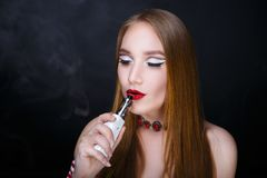 Girl smokes electronic cigarette. Young beautiful woman girl lady smokes electronic cigarette. model fashionable hairdo, professional makeup red color trendy Royalty Free Stock Photo