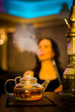 Girl smokes a hookah and drink tea in the bar Stock Image
