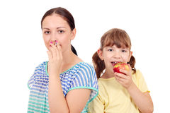 Girl smoking a cigarette and a little girl eating an apple Stock Photography