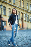 A girl in sneakers, jeans and a leather jacket stands on a city Royalty Free Stock Photography