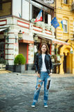 A girl in sneakers and a leather jacket stands on the street in Royalty Free Stock Image