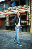 A girl in sneakers and a leather jacket walks down the street am Royalty Free Stock Photo